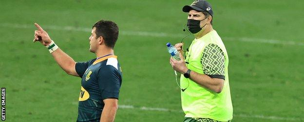 Rassie Erasmus acting as a waterboy during a game