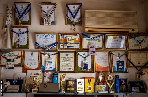 Medals and awards on Al Hussein's wall inside his flat in Athens